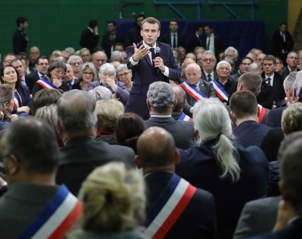 "French President Emmanuel Macron gestures as he speaks during a meeting gathering some 600 mayors who will relay the concerns aired by residents in their towns and villages in the Normandy city of Grand Bourgtheroulde on January 15, 2019, as part of the official launch of the ""great national debate"", a central plank of French President Emmanuel Macron bid to turn around his embattled presidency since the yellow vest (gilet jaune) movement protests. - The meeting sounds the start of two months of public consultations in towns and villages across the country on four main themes: taxation; France's transition to a low-carbon economy; democracy and citizenship, and the functioning of the state and public services. (Photo by Ludovic MARIN / AFP)"